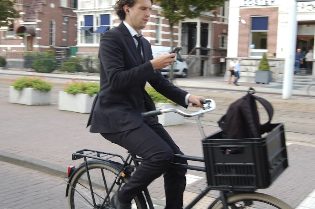 a man cycling in a business suit in amsterdam