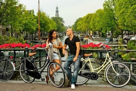 man and woman on canal in amsterdam with two vintage bikes