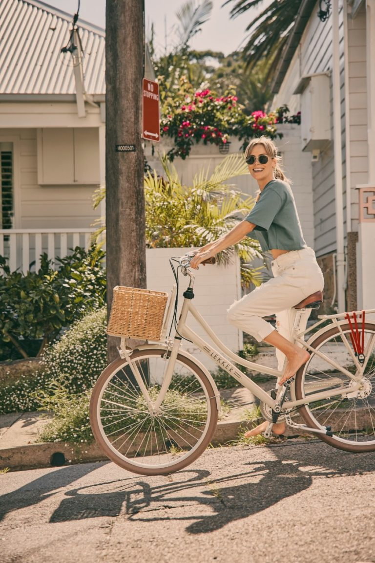 Young woman wearing sunglasses and casual clothes riding bicycle with basket down a hill while smiling