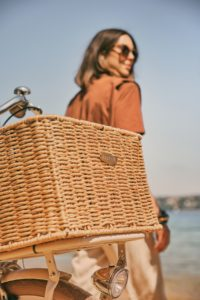 Young woman with sunglasses with bicycle with basket at the beach