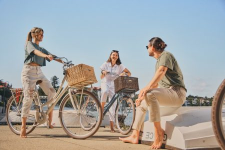 Group of people riding bicycles with baskets on the beach