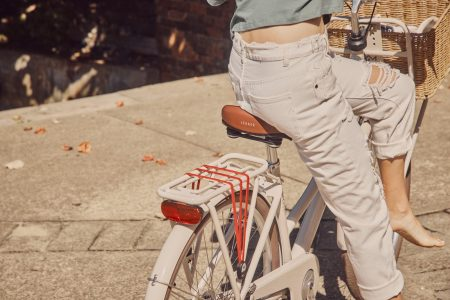 Woman seen from the back wearing jeans riding a bicycle with basket
