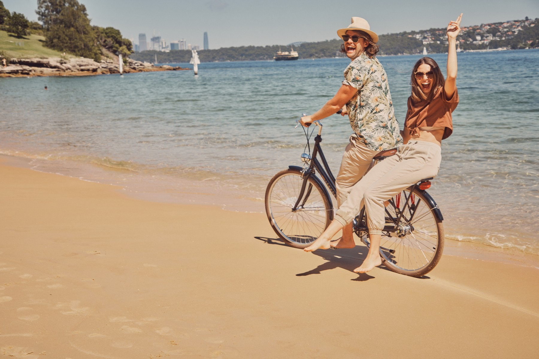 Young woman and young man wearing sunglasses riding one bicycle at the beach having fun