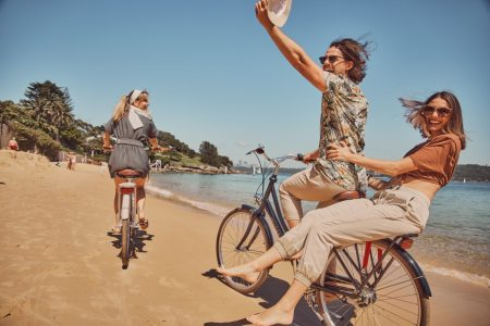 Group of two young women and one young man wearing sunglasses laughing and smiling and riding bicycles on the beach