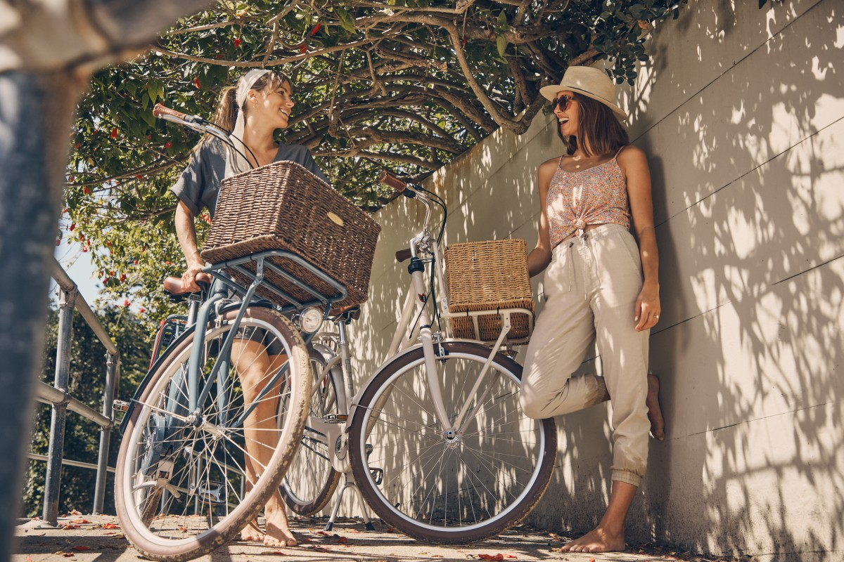 Two young women wearing sunglasses and casual clothes talking next to bicycles with baskets