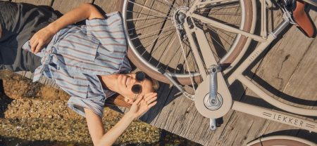 Young woman wearing sunglasses and casual clothes laying in the sun on a bridge at the beach with bicycle