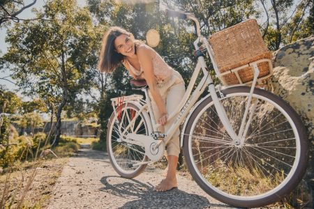 Young woman smiling and wearing casual clothes in nature with bicycle with basket