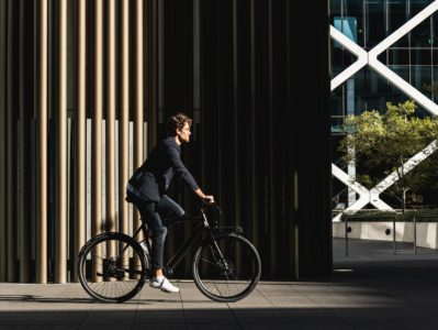 Man wearing jeans and white sneakers riding black bicycle