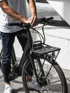 Man with casual clothing holding black bicycle handlebar with front rack
