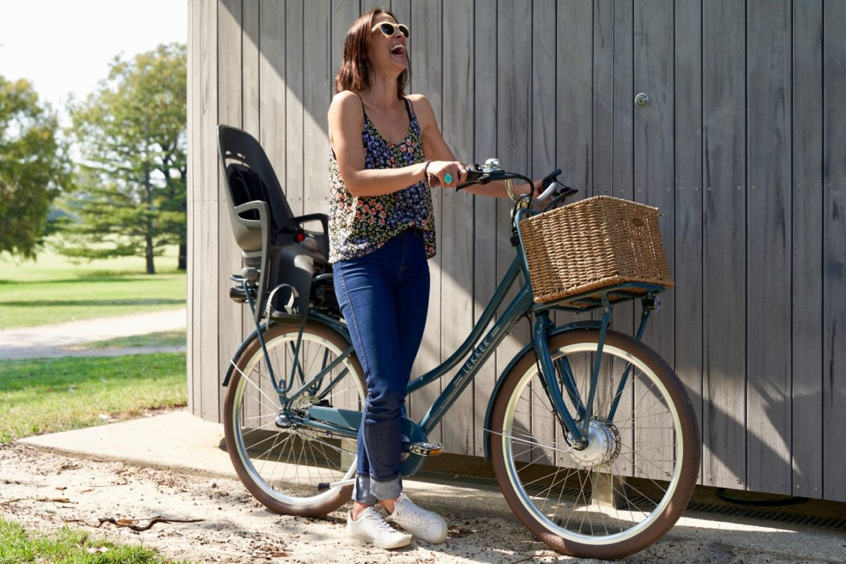 Young woman wearing sunglasses next to bicycle laughing